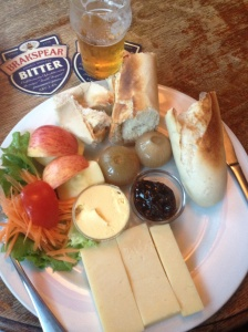 A ploughman's lunch, the field workers' traditional selection: cheese, bread, butter, chutney, pickled onions, apples and some veggies. Sometimes ham, too. The beer was a lager of some sort, not what the coaster boasts.